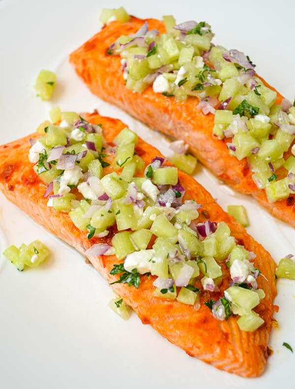 2 servings of plated parchment baked harissa salmon with cucumber relish spooned on top of salmon