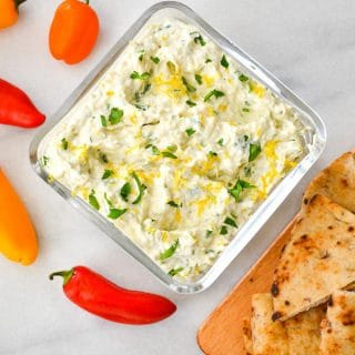 overhead of quick and easy artichoke dip with flatbread and mini peppers