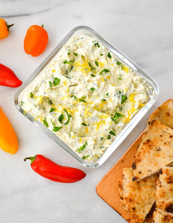 Overhead shot of artichoke dip in bowl with flatbread and mini peppers