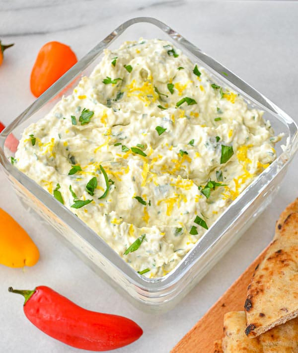 close up of artichoke dip garnished with lemon zest and parsley